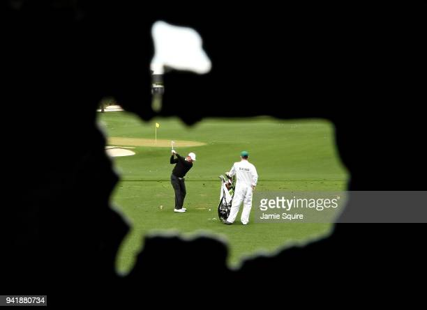 Jose Maria Olazabal of Spain warms up on the range as caddie Michael Batty looks on during a practice round prior to the start of the 2018 Masters...