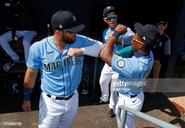 Jose Marmolejos and Shed Long Jr. #4 of the Seattle Mariners greet in the dugout prior to a Cactus League spring training baseball game against the...