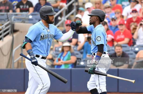 Jose Marmolejos of the Seattle Mariners celebrates with Dee Gordon after hitting a two run home run against the Los Angeles Angels during the second...