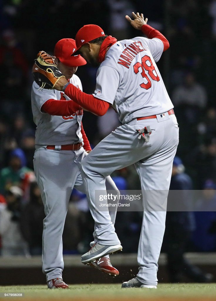 Jose Martinez #38 and Jedd Gyorko #3 of the St. Louis Cardinals celebrate a win over the Chicago Cubs at Wrigley Field on April 17, 2018 in Chicago, Illinois. The Cardinals defeated the Cubs 5-3.
