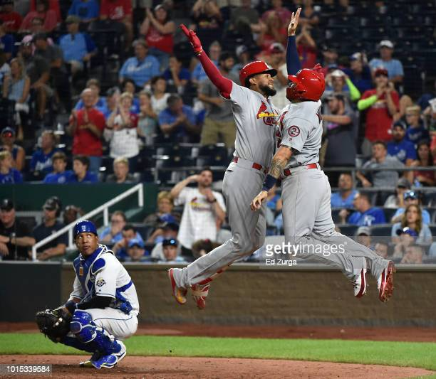 Jose Martinez of the St Louis Cardinals celebrates his tworun home run with Yadier Molina as Salvador Perez of the Kansas City Royals looks on in the...