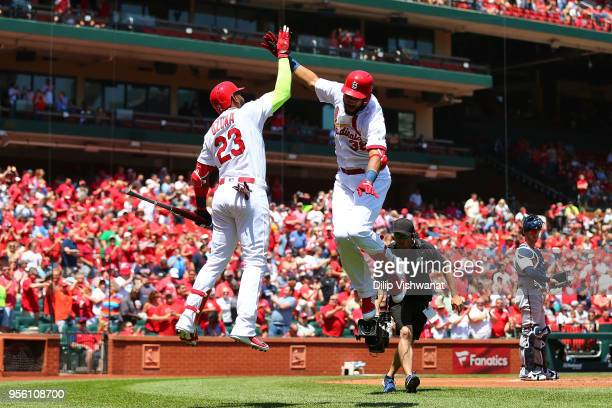 Jose Martinez of the St Louis Cardinals celebrates with Marcell Ozuna after hitting a home run against the Minnesota Twins in the first inning at...