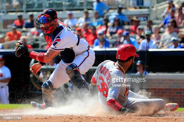 Jose Martinez of the St Louis Cardinals slides into home to score before the tag by Tyler Flowers of the Atlanta Braves during the eighth inning at...