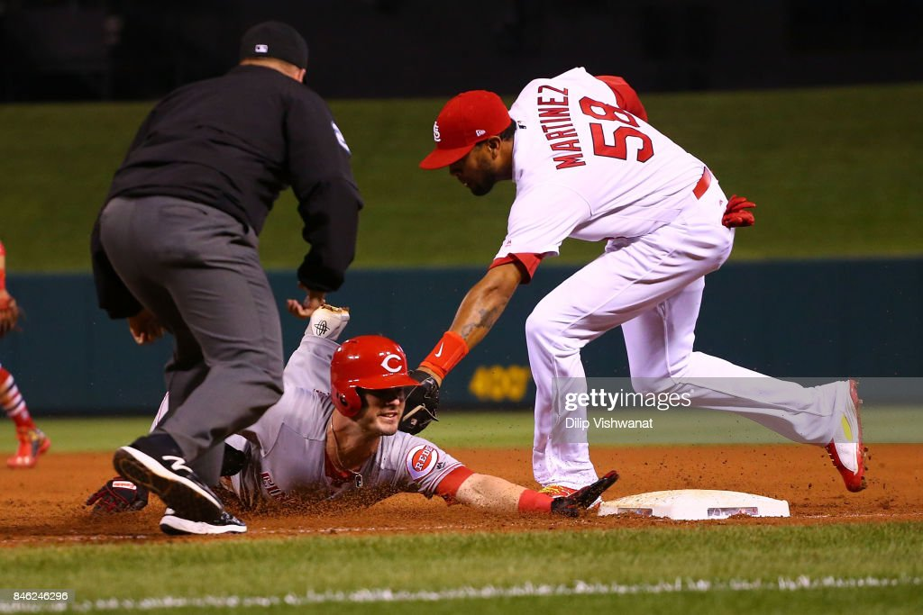 Jose Martinez #58 of the St. Louis Cardinals tags out Jesse Winker #33 of the Cincinnati Reds at first base after a run down in the fifth inning at Busch Stadium on September 12, 2017 in St. Louis, Missouri.