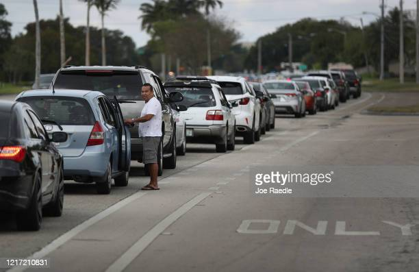 Jose Martinez waits in line next to his car to receive groceries provided by the food bank Feeding South Florida and distributed by the City of...