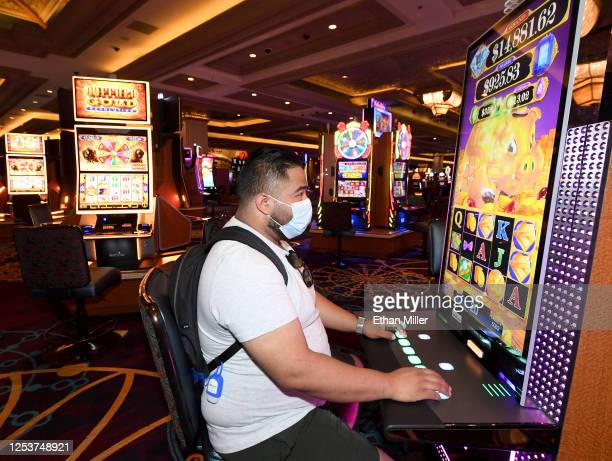 Jose Medina of Texas wears a mask as he plays a slot machine at Mandalay Bay Resort and Casino after the Las Vegas Strip property opened for the...