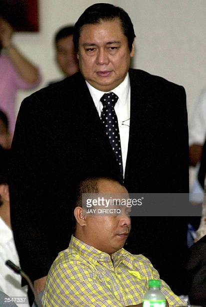 Jose Miguel Arroyo husband of President Gloria Arroyo and star witness Eugenio Mahusay take their seats 02 September 2003 at the start of a Senate...