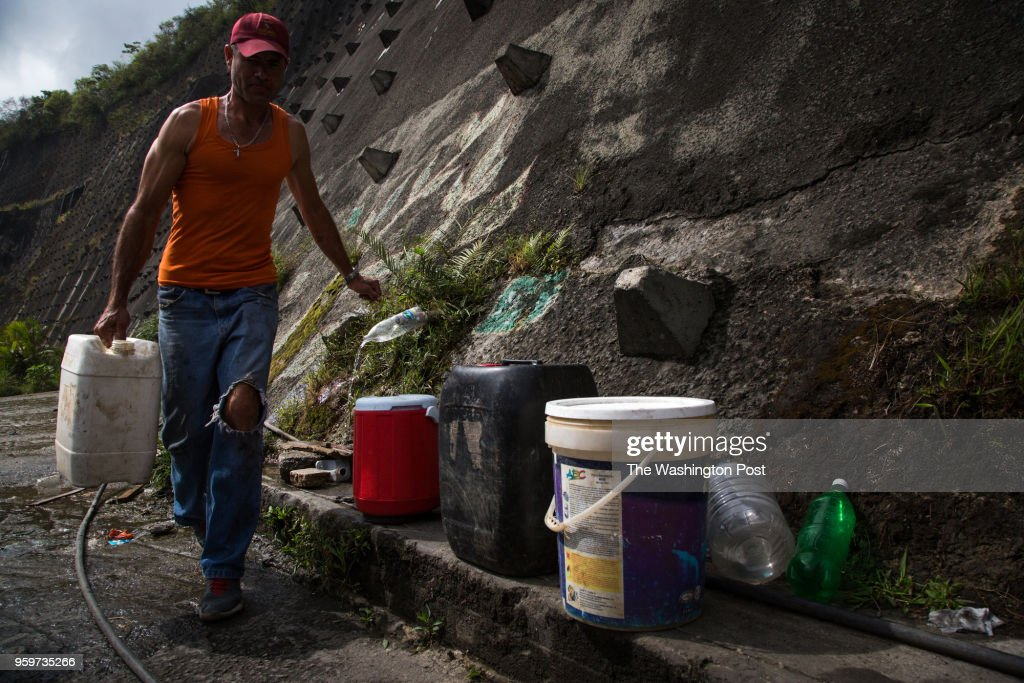Jose Miguel Pereira, 45, carries a water containers from a mounting spring in the highway tha connect Caracas city and Guarenas. They have more than a month without water service in their house at Ciudad Mariche community