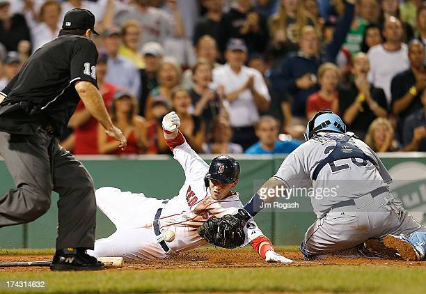 Jose Molina of the Tampa Bay Rays drops the ball as Stephen Drew of the Boston Red Sox scores in the 8th inning at Fenway Park on July 23 2013 in...