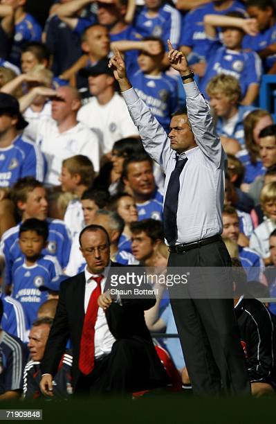 Jose Mourinho manager of Chelsea gestures to his players as Rafael Benitez manager of Liverpool looks at his watch during the Barclays Premiership...