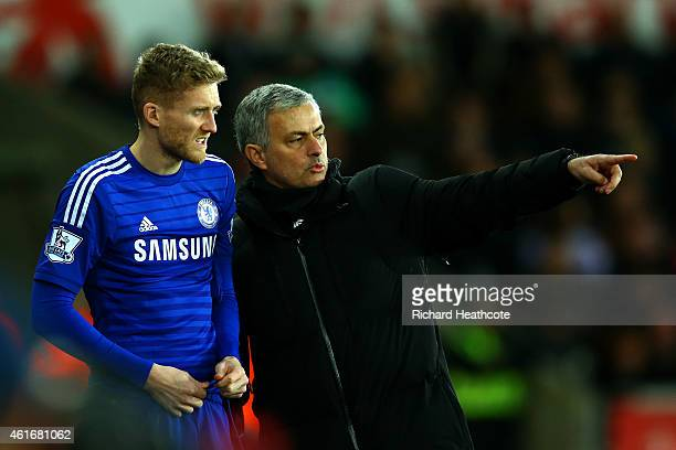 Jose Mourinho, manager of Chelsea speaks with Andre Schuerrle of Chelsea as he prepares to gon on during the Barclays Premier League match between...