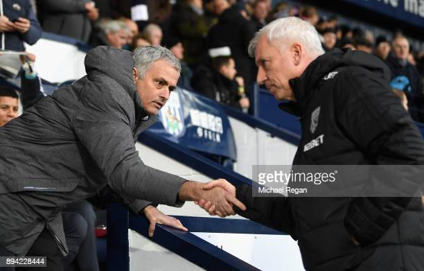 Jose Mourinho Manager of Manchester United and Alan Pardew Manager of West Bromwich Albion greet each other prior to the Premier League match between...