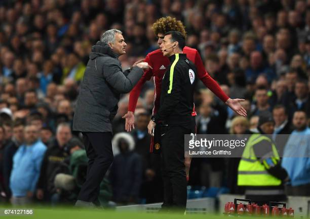 Jose Mourinho Manager of Manchester United and Marouane Fellaini of Manchester United speak to the 4th official following a red card for Marouane...