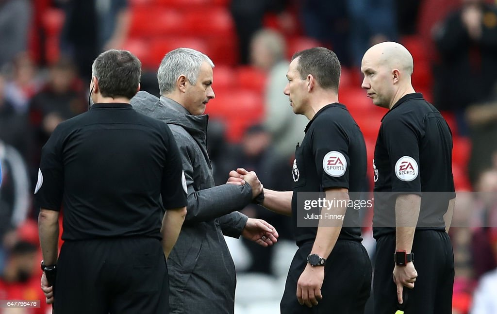 Jose Mourinho, Manager of Manchester United (L) and referee Kevin Friend (C) embrace after the Premier League match between Manchester United and AFC Bournemouth at Old Trafford on March 4, 2017 in Manchester, England.