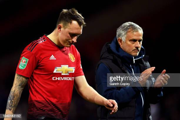 Jose Mourinho Manager of Manchester United applauds fans as Phil Jones of Manchester United looks dejected after missing his team's eighth penalty...