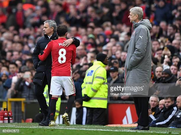 Jose Mourinho Manager of Manchester United embraces Juan Mata of Manchester United after he is subbed off for Morgan Schneiderlin of Manchester...