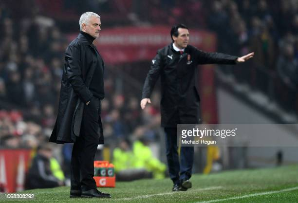 Jose Mourinho Manager of Manchester United looks on as Unai Emery Manager of Arsenal gives his team instructions during the Premier League match...