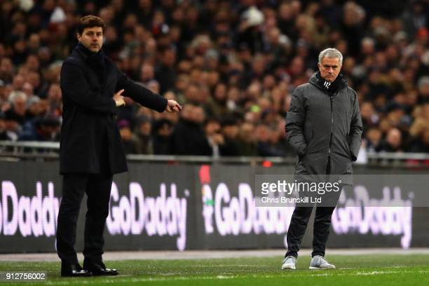 Jose Mourinho Manager of Manchester United looks on from the sideline next to Mauricio Pochettino Manager of Tottenham Hotspur during the Premier...