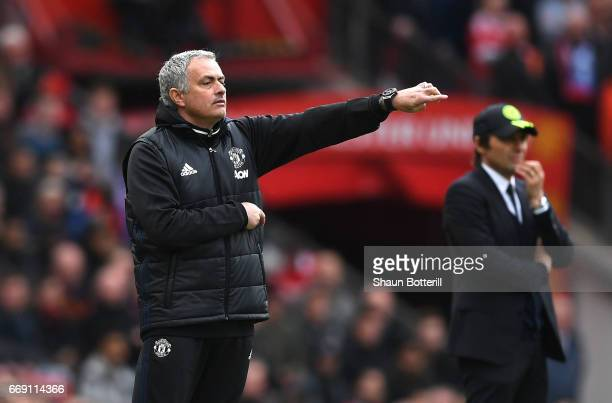 Jose Mourinho manager of Manchester United signals as Antonio Conte manager of Chelsea looks on during the Premier League match between Manchester...