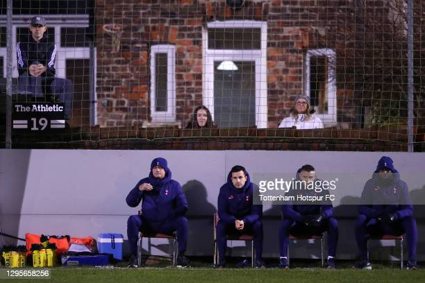 Jose Mourinho, Manager of Tottenham Hotspur and backroom staff look on from the pitch side as fans are seen watching the game from back gardens in...