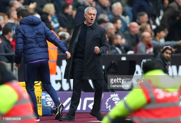 Jose Mourinho Manager of Tottenham Hotspur embraces his coaching staff after his side score their first goal during the Premier League match between...