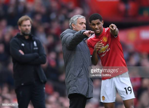 Jose Mourinho of Manchester United speaks to Marcus Rashford as Jurgen Klopp of Liverpool looks on during the Premier League match between Manchester...