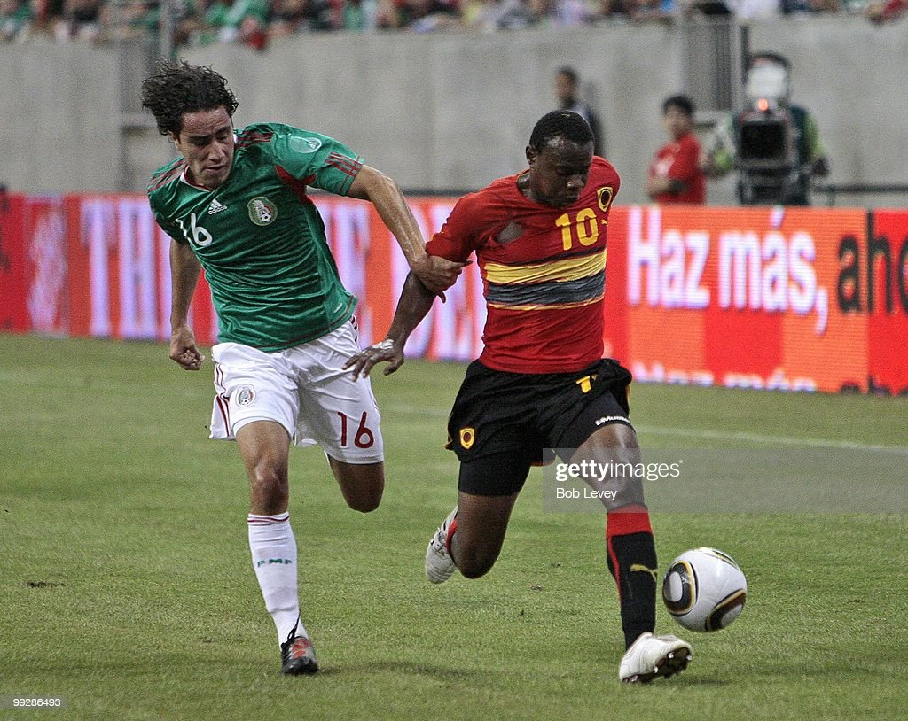 Jose #10 of Angola fends off Efrain Juarez #16 of Mexico during the friendly international match between Mexico and Angola at Reliant Stadium on May 13, 2010 in Houston, Texas.