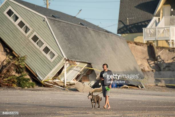 Jose Orosz walks his dog Karen by a beachfront home destroyed by Hurricane Irma on September 13 2017 in Vilano Beach Florida Nearly 4 million people...