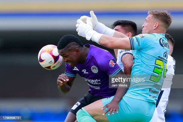 Jose Ortiz and Nicolas Vikonis , goalkeeper of Mazatlan fight for the ball with Emanuel Montejano of Pumas during the 2nd round match between Pumas...