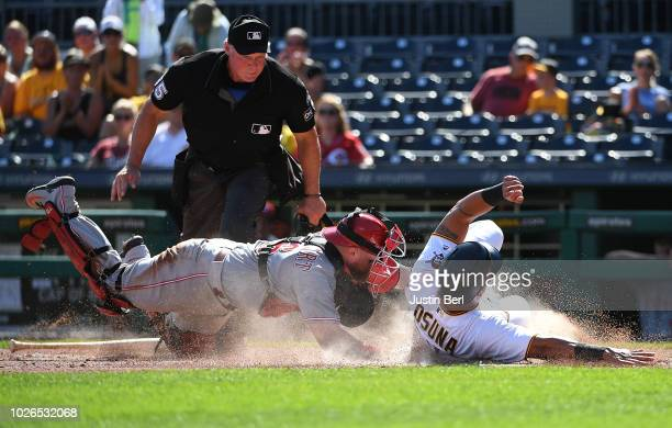 Jose Osuna of the Pittsburgh Pirates slides safely into home plate past Tucker Barnhart of the Cincinnati Reds in the seventh inning during the game...