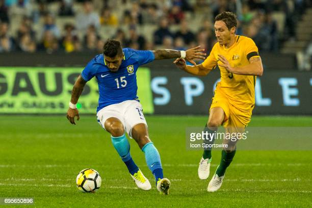 Jose Paulo Marcela Junior of the Brazilian National Football Team controls the ball in front of Mark Milligan of the Australian National Soccer Team...