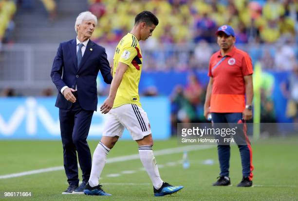 Jose Pekerman Head coach of Colombia speaks to James Rodriguez of Colombia who looks dejected as he is substituted off due to injury during the 2018...