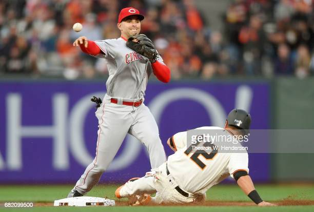 Jose Peraza of the Cincinnati Reds completes the double-play getting his throw off over the top of Joe Panik of the San Francisco Giants in the...