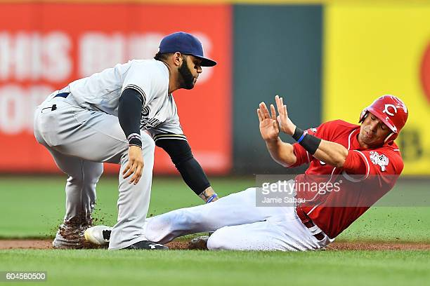 Jose Peraza of the Cincinnati Reds is tagged out by Jonathan Villar of the Milwaukee Brewers while trying to steal second base in the first inning at...