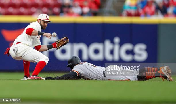 Jose Peraza of the Cincinnati Reds misses the throw as Kevin Pillar of the San Francisco Giants slides safely into second base at Great American Ball...