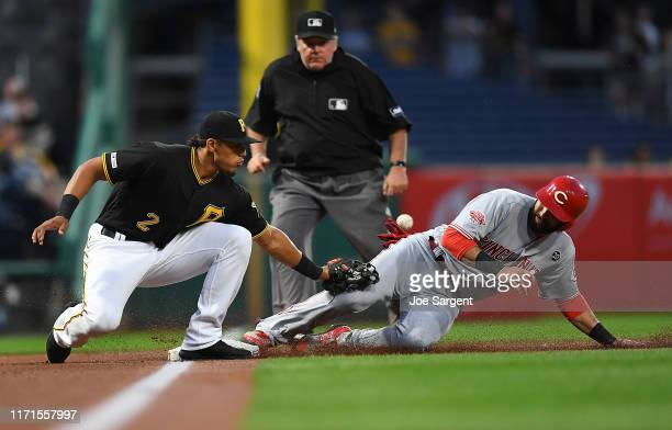 Jose Peraza of the Cincinnati Reds safely steals third base in front of Erik Gonzalez of the Pittsburgh Pirates and scores on an error during the...
