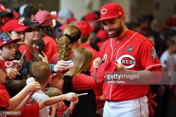 Jose Peraza of the Cincinnati Reds signs autographs for young fans before a game against the Pittsburgh Pirates as part of Kids Opening Day at Great...