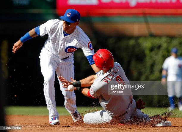 Jose Peraza of the Cincinnati Reds steals second base as Addison Russell of the Chicago Cubs is unable to catch the throw from Willson Contreras...
