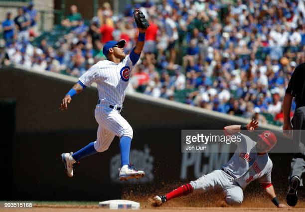 Jose Peraza of the Cincinnati Reds steals second base as Addison Russell of the Chicago Cubs takes the throw during the fourth inning at Wrigley...