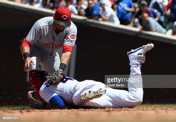 Jose Peraza of the Cincinnati Reds tags out Willson Contreras of the Chicago Cubs at second base during the third inning on July 8, 2018 at Wrigley...