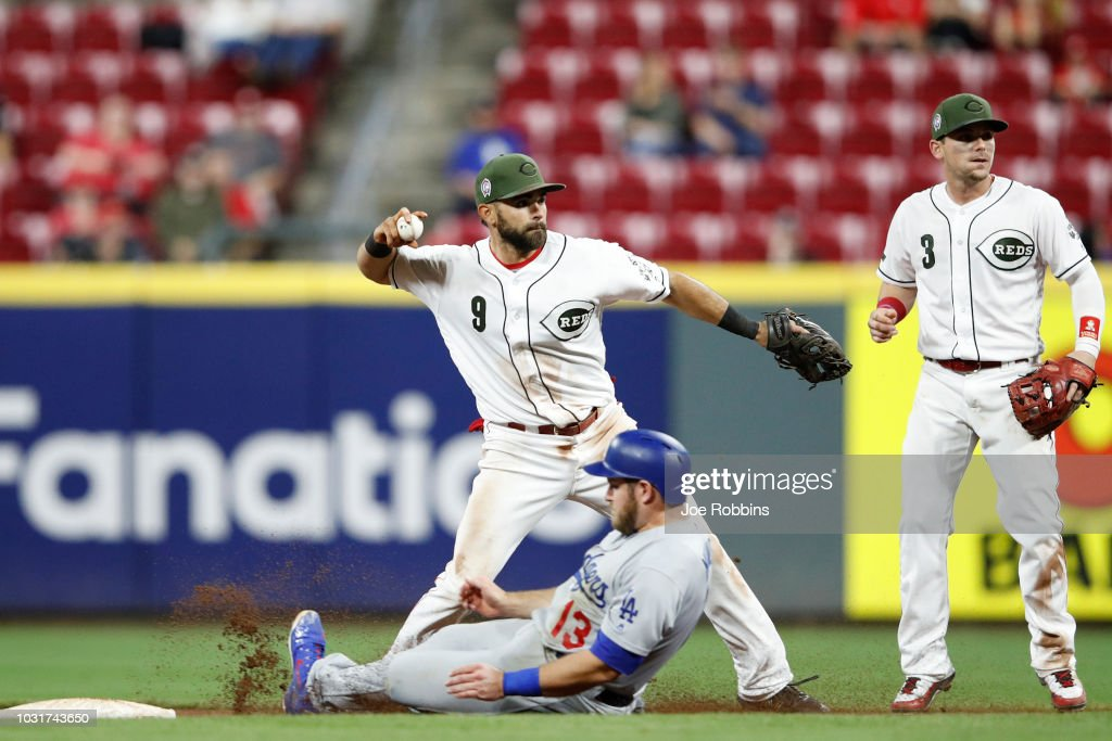 Jose Peraza #9 of the Cincinnati Reds turns a double play ahead of the slide by Max Muncy #13 of the Los Angeles Dodgers in the eighth inning at Great American Ball Park on September 11, 2018 in Cincinnati, Ohio. The Reds won 3-1.