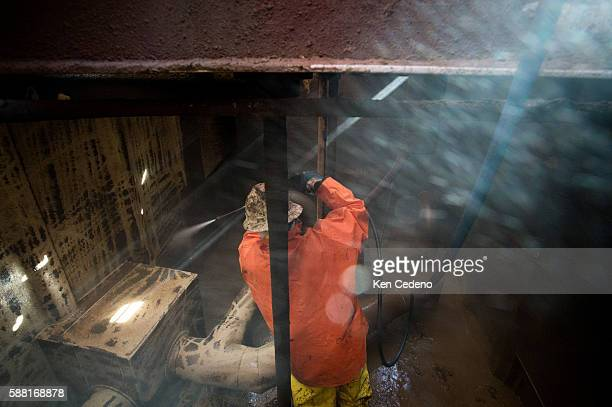 Jose Perez a floor hand power sprays a storage tank after vacuuming out the remaining sediment on the Raven Oil Drilling rig near Watford City ND Oct...