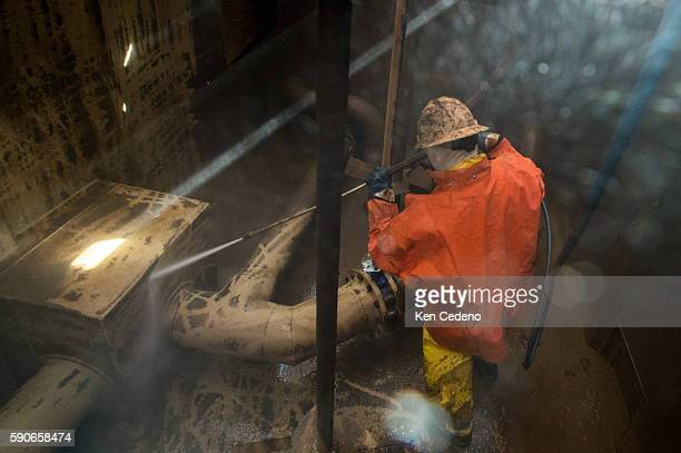 Jose Perez a floor hand power sprays a storage tank of the remaining sediments of drilling fluid mud from a tank on the Raven Drilling rig near...