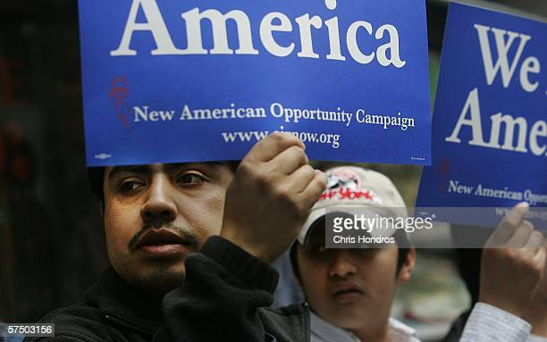 Jose Perez and friend Benancio Martez both Mexican laborers working in Chinese restaurant in Chinatown hold signs during a sidewalk rally against...