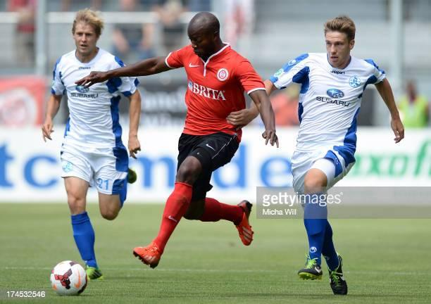 Jose Pierre Vunguidica of Wiesbaden is challenged by Kai Bastian Evers of Stuttgart and Marc Stein of Stuttgart during the Third League match between...