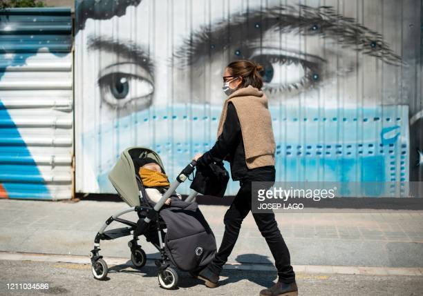 Jose pushes her son Pol's stroller past a mural depicting a person wearing a face mask, on April 26 in Barcelona, during a national lockdown to...