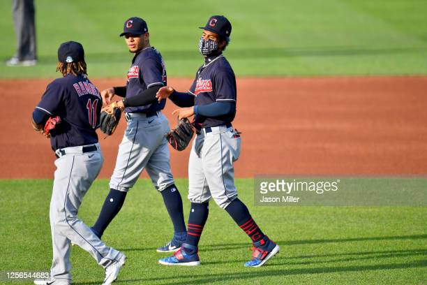 Jose Ramirez and Cesar Hernandez talk with Francisco Lindor of the Cleveland Indians as the walk to their positions during the second inning of an...