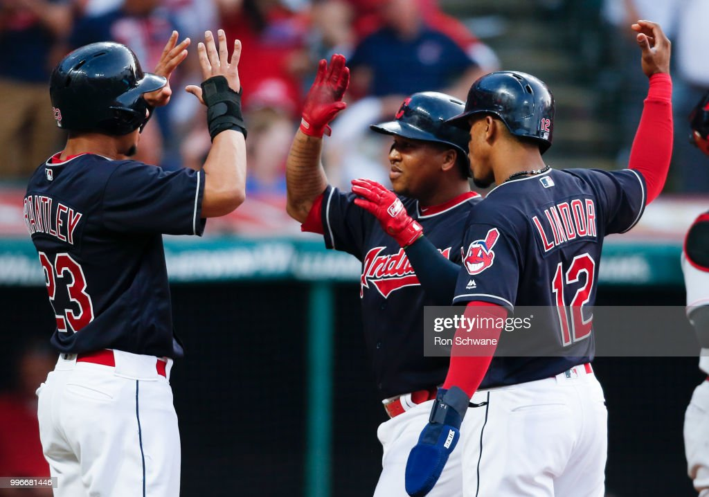 Jose Ramirez #11 of the Cleveland Indians celebrates with Michael Brantley #23 and Francisco Lindor #12 after hitting a three run home run off Tanner Rainey #44 of the Cincinnati Reds during the third inning at Progressive Field on July 11, 2018 in Cleveland, Ohio.
