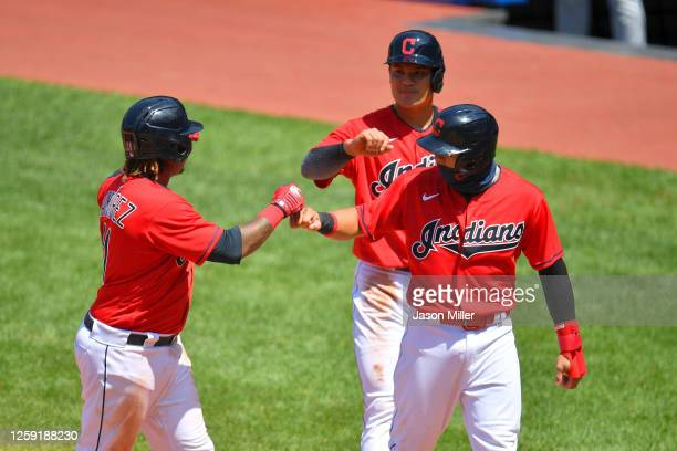 Jose Ramirez of the Cleveland Indians celebrates with Yu Chang and Cesar Hernandez after all scored on a homer by Ramirez during the fourth inning...