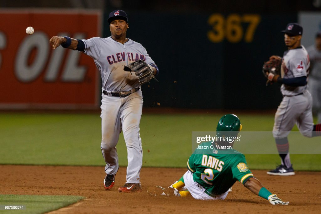 Jose Ramirez #11 of the Cleveland Indians completes a double play over Khris Davis #2 of the Oakland Athletics during the eighth inning at the Oakland Coliseum on June 29, 2018 in Oakland, California. The Oakland Athletics defeated the Cleveland Indians 3-1.